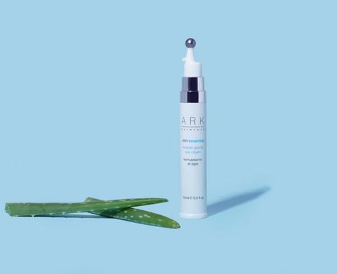 Image: ARK Skincare's Reverse Gravity Eyecream next to Aloe Vera on a blue back backdrop.