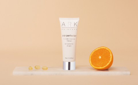 Image: ARK Skincare's Hydration Injection Masque on a marble slate with an orange half and vitamin capsules