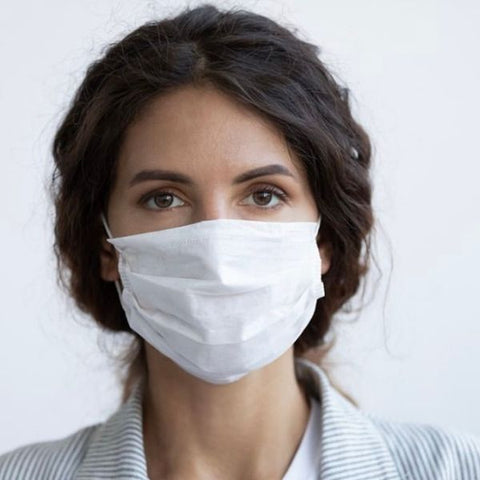 Image: Woman wearing a white disposable mask to cover her nose and mouth