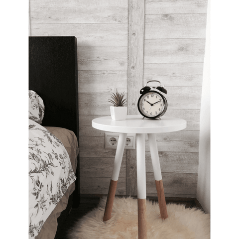 Image of a white wooden bedside table holding an alarm clock and small plant