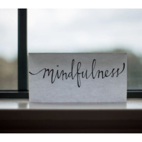 "Image: White reminder card with hand written note which reads ""mindfulness"" on a window ledge."