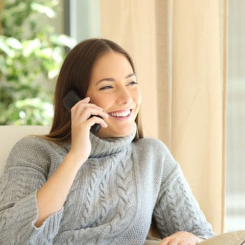 Young brunette woman smiling while chatting on the phone