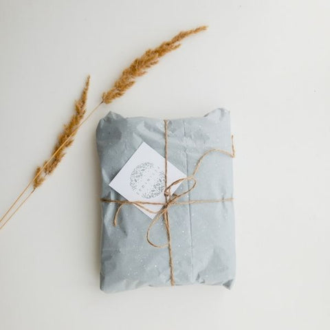 Gift wrapped in grey packing paper with a bow tied in string