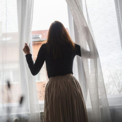 Woman pulling back white netting curtains to look out of a window