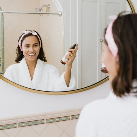 Woman applying her skincare products in front of a bathroom mirror