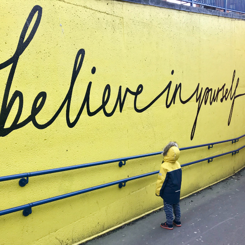 A wall spray-painted with a positive quote: believe in yourself