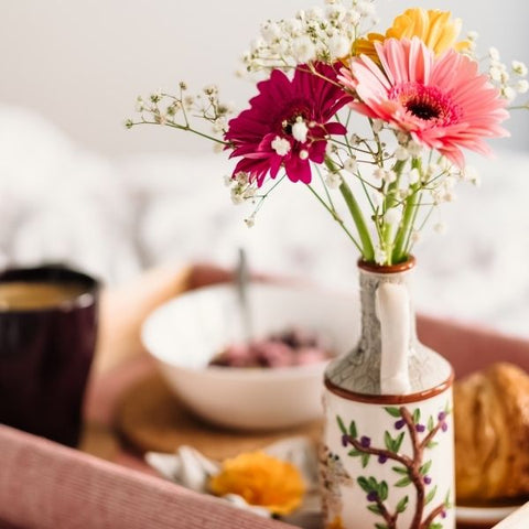 A vase of flowers on a breakfast tray with cereal and pastries