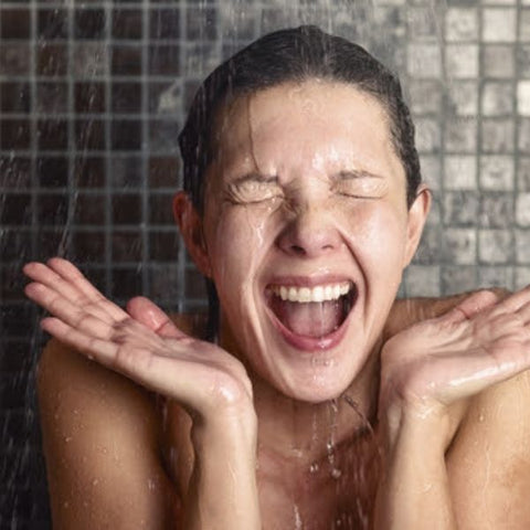 A woman laughing and looking shocked as she showers in cold water