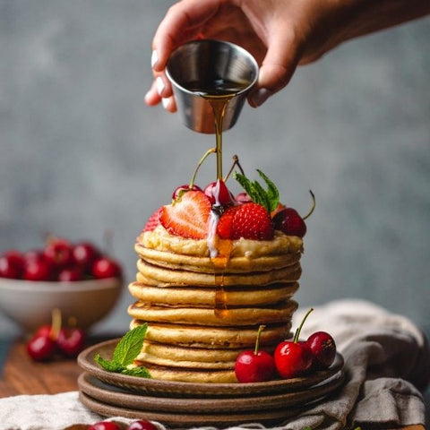 Stack of vegan pancakes with berries drizzled in maple syrup