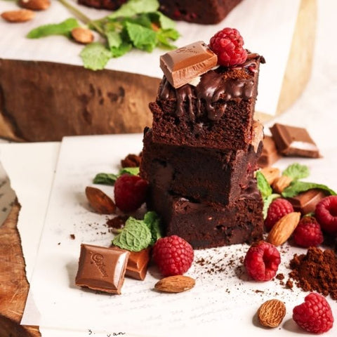 A stack of home-made chocolate brownies with raspberries and chocolate