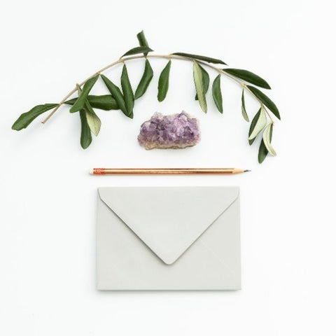 A sheet of paper, white envelope, pencil and paper weight to write somebody a letter