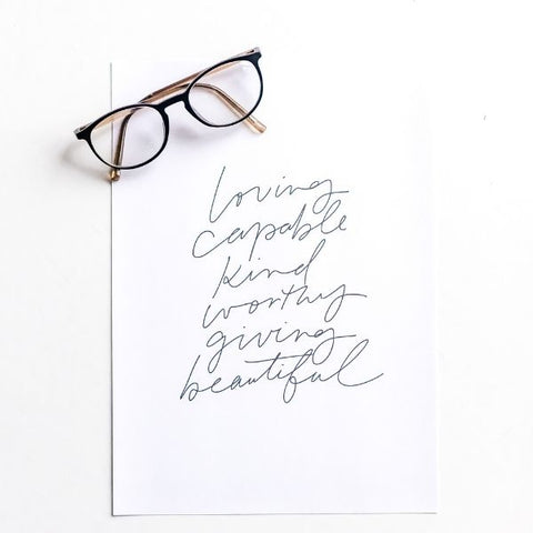 A pair of glasses laid on top of a self-love poster print with encouraging affirmations