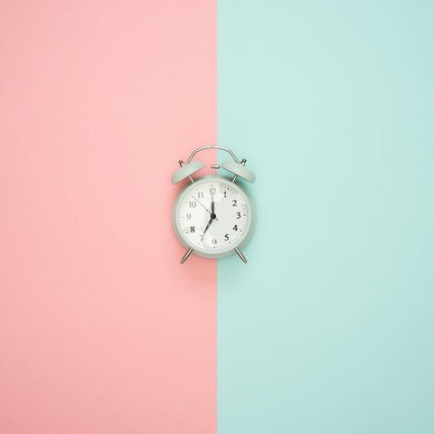 A pink and blue flat lay with an old fashioned duck egg coloured alarm clock