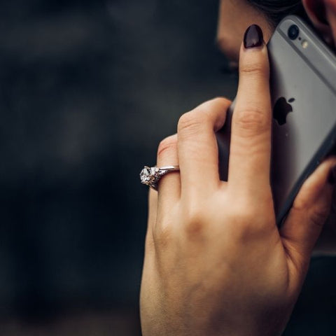A woman holding a space grey iphone to her ear and talking on the phone