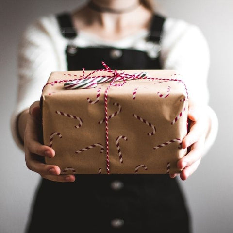 Woman holding a hand wrapped christmas gift in sustainable wrapping paper