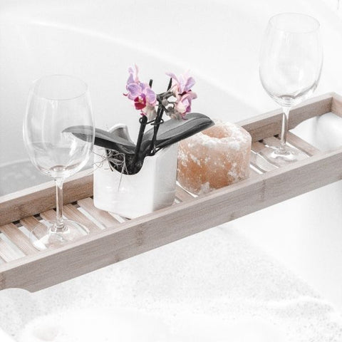 A wooden bath tray laid across a white bath tub holding a small flower and glass of wine