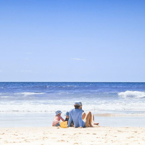 Family sitting on a sandy beach by the sea in the sunshine