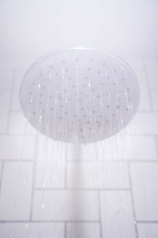 Image: Water streaming from shower head against white bathroom tiles