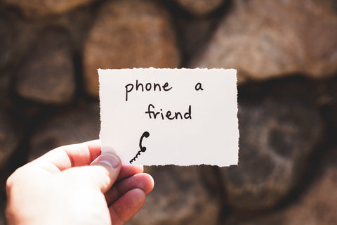 "Image: Person's hand holding a note out in front of them saying ""phone a friend"""