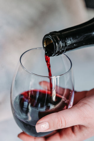 Image: Woman pouring a glass of red wine