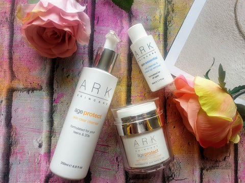 Selection of ARK Skincare's Protect and Skin Essential products next to floral arrangement