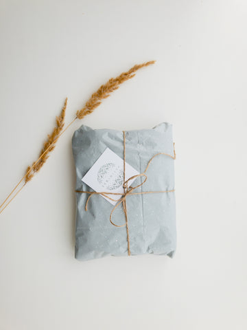 Image: Gift wrapped up in parcel paper with a string bow and gift card.