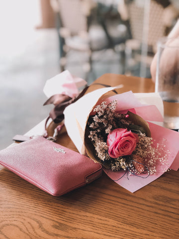 Image: Pink roses wrapped up in tissue paper next to a purse laid on a wooden table