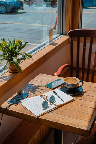 Image: Wooden coffee table holding a cup of coffee, phone, sunglasses and a handwritten diary