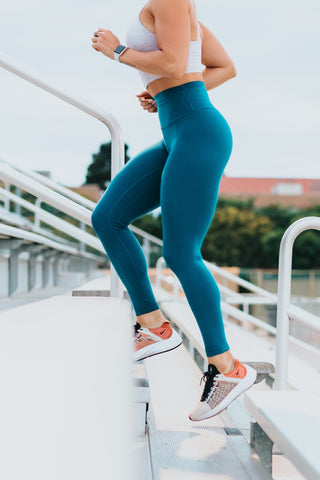 A lady wearing sports leggings and trainers running up some outdoor steps