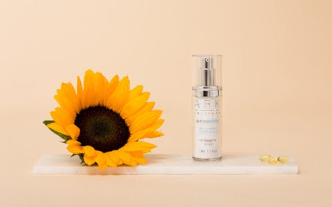 ARK skincare's SPF 30 Primer laid next to a sunflower