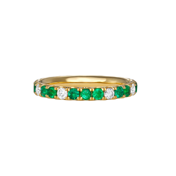 Thin yellow gold ring with emeralds and diamonds surrounding the entire band.