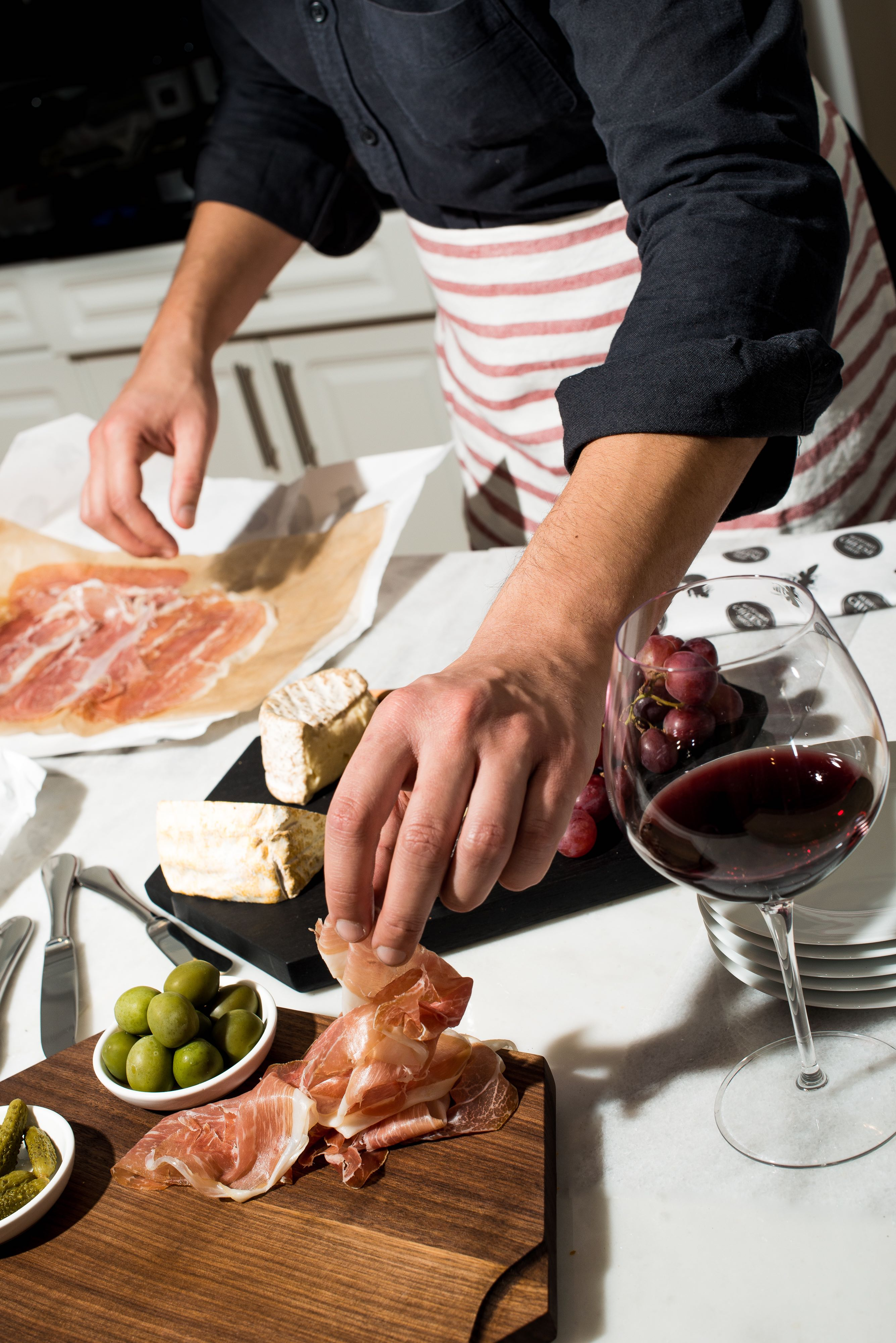 Don't forget all the additions to your cheese board —olives, proscuitto, and bread.