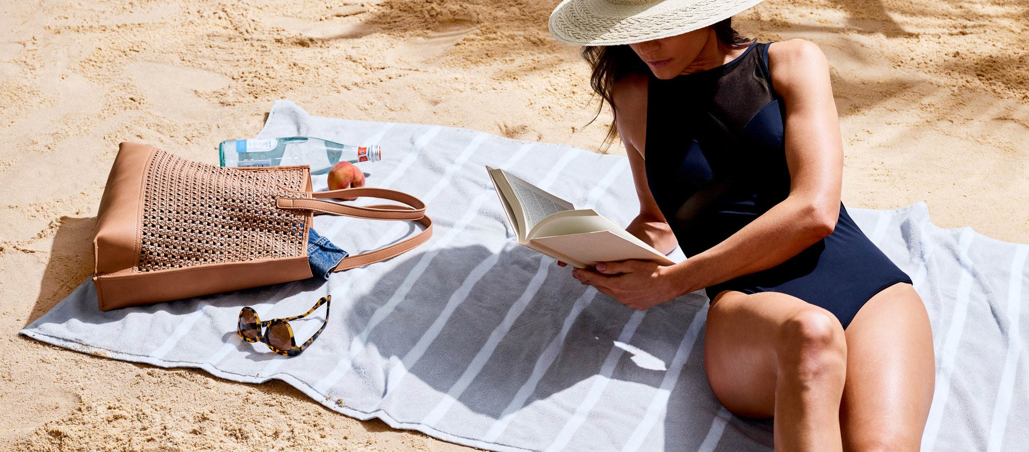 Woman on beach reading book