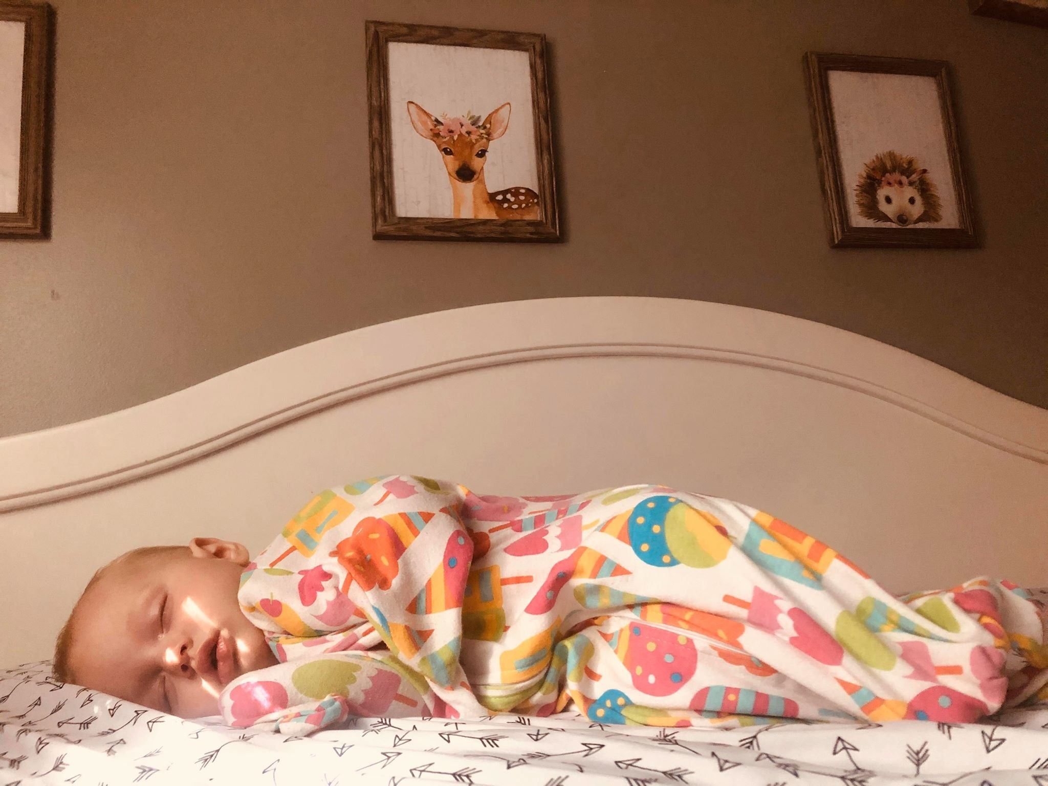 Happy baby in safe sleep swaddle alternative after transitioning