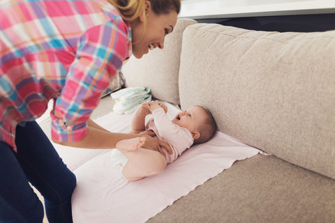 M​other swaddling a baby before swaddle transition period