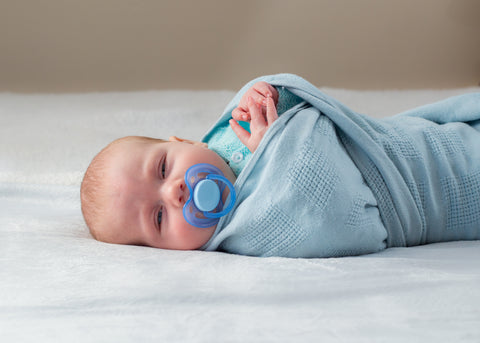 Newborn baby sleeping in swaddle before swaddle transition