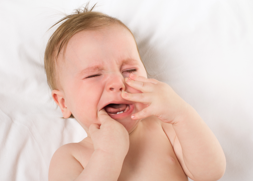 Example of unhappy baby crying at night while teething with first tooth