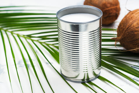 can of coconut milk with 2 coconuts and a green leaf