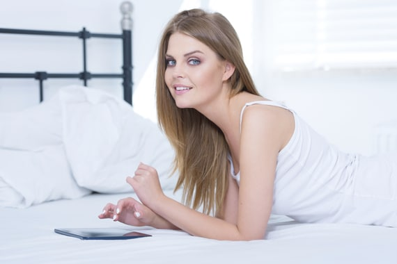 Pretty girl lying on her stomach in bed using a smart tablet