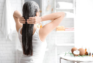 A woman applying Coconut Oil in her long black hair to promote a healthy hair care routine