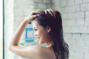 Woman with long dark hair smiling and doing a scalp treatment in the shower