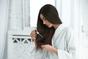 Woman using serum dropper to apply oil to the ends of her dark hair.