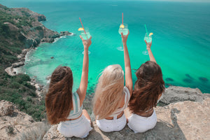 Three women with long healthy hair sitting on a rock overlooking the ocean, holding glasses up to the hair.