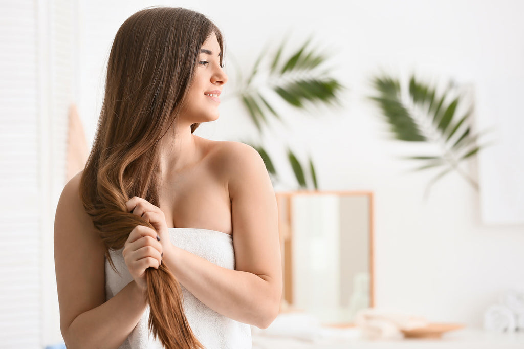 Woman with long brown hair caring for her hair extensions using vegan and cruelty-free hair care products.