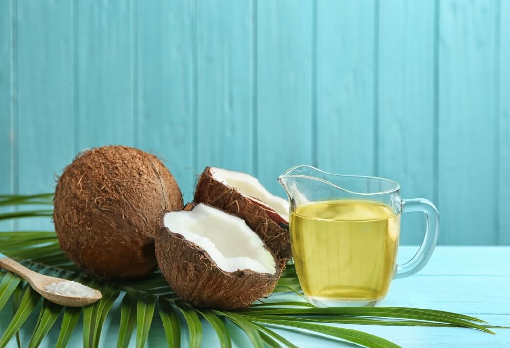 A whole coconut, halved coconut and a measuring cup of coconut oil sitting on top of a counter waiting to be used in a hair care routine