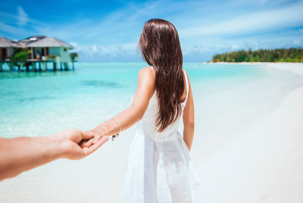 Woman with long brown hair walking on a tropical beach with azure blue water as she holds hands with the person behind the camera taking the photo.