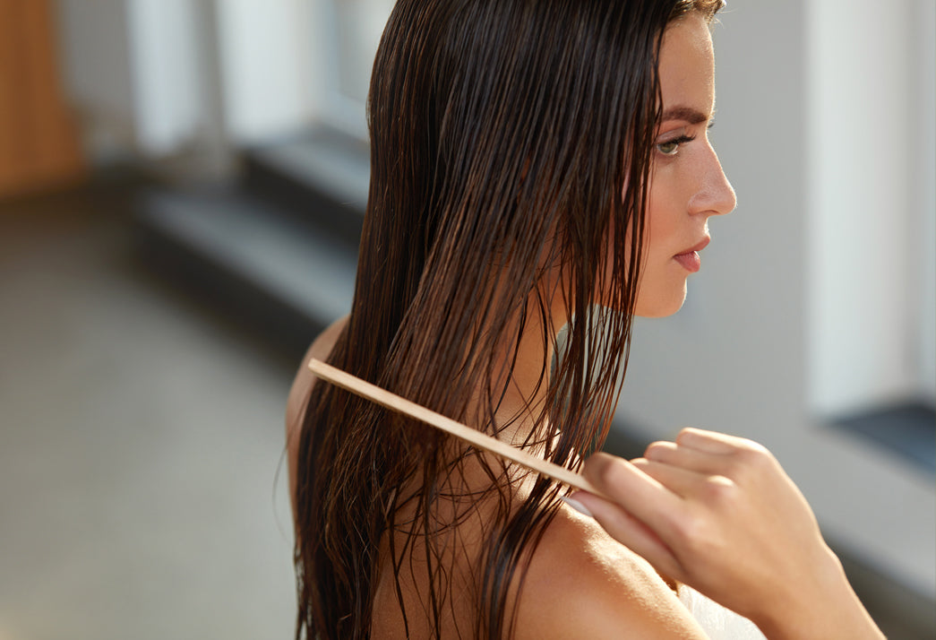 A model doing a hair mask at home by applying oil to her hair and combing the strands for healthy long hair
