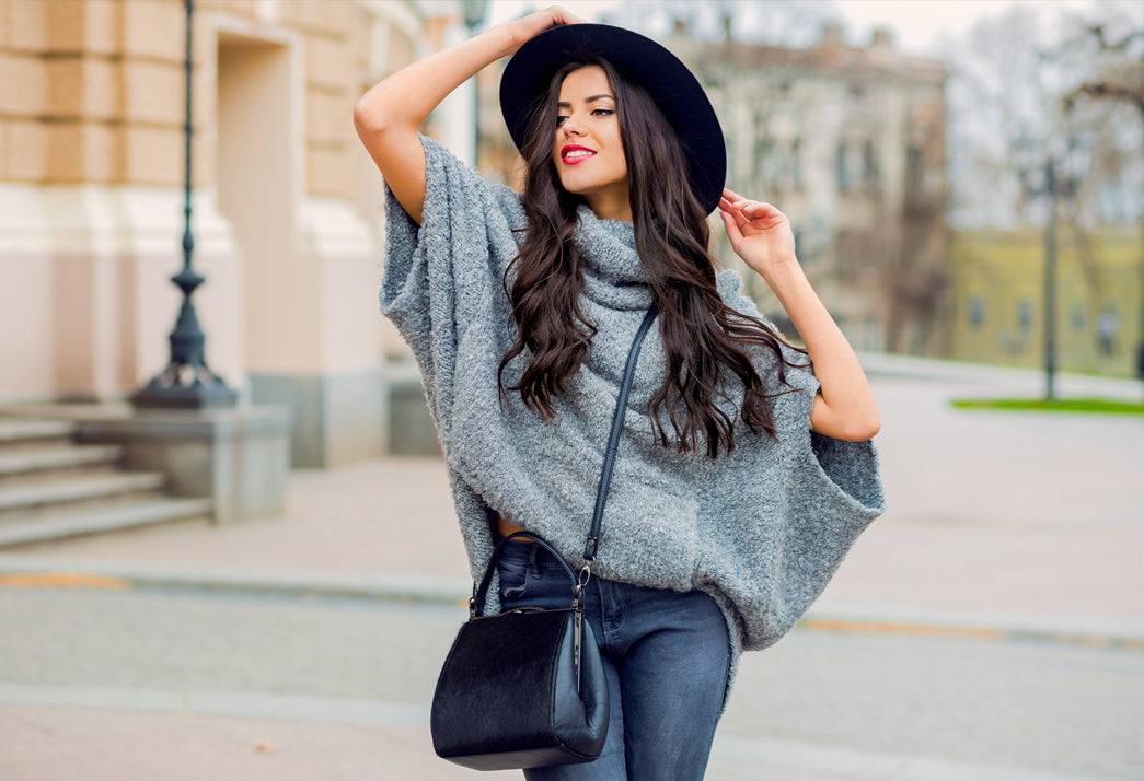 A model with long hair is wearing a hat and big sweater during fall season