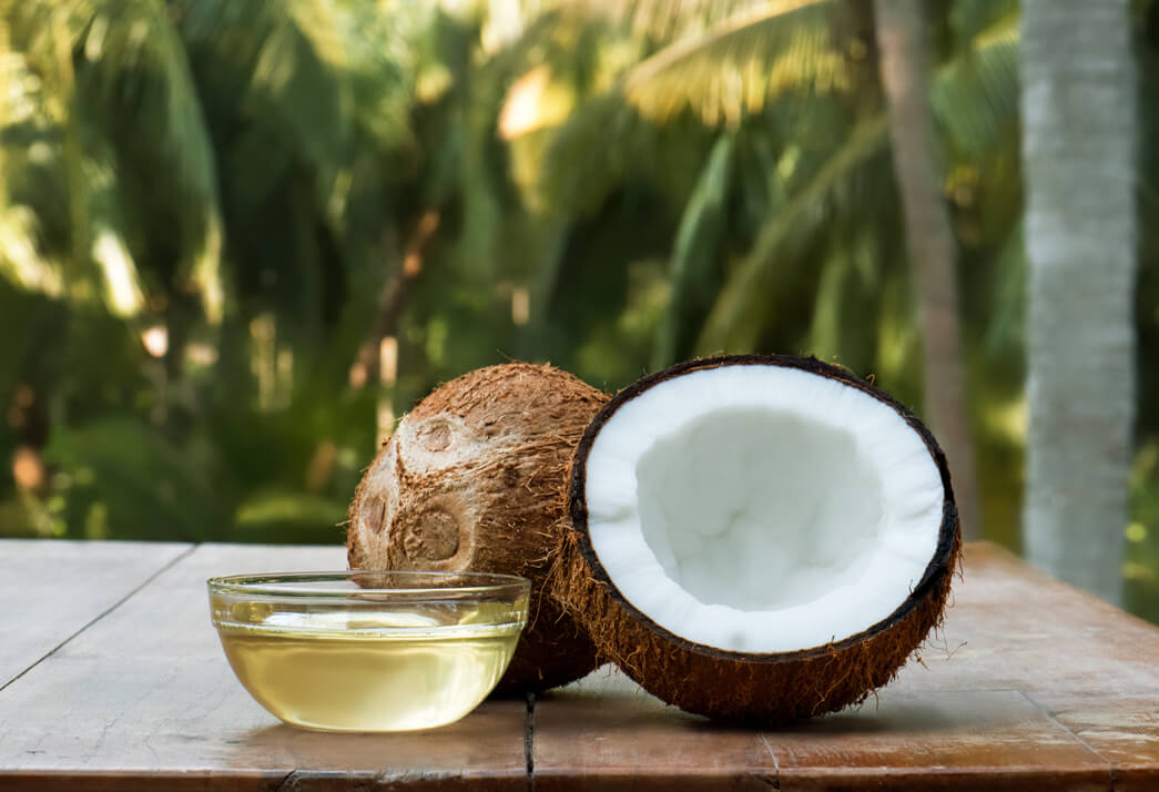 A coconut fruit cut in half with a coconut oil in a glass bowl that is ready to apply to the hair