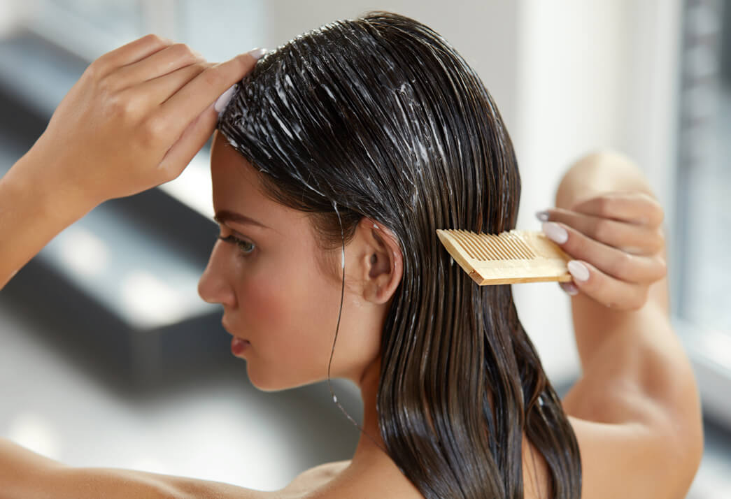 A girl combing her ST. TROPICA Coconut Oil Hair Mask in her hair to remove tangles
